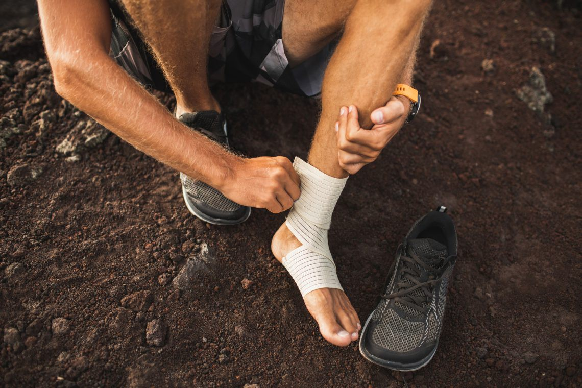 a man wrapping his foot before a workout due to pain