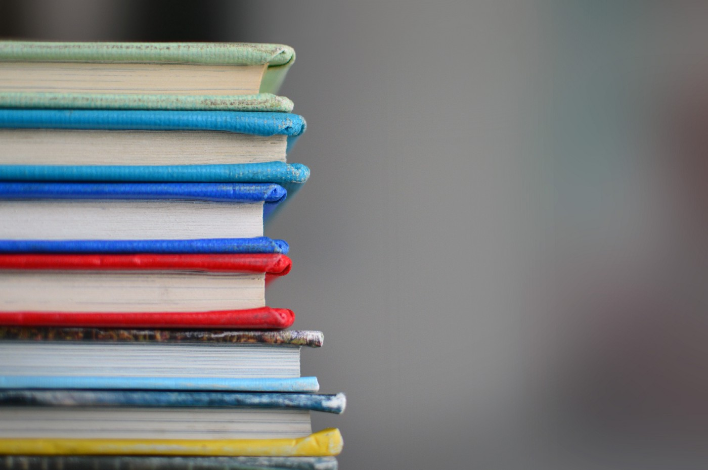 A stack of six books with multi-colored spines and pages showing.