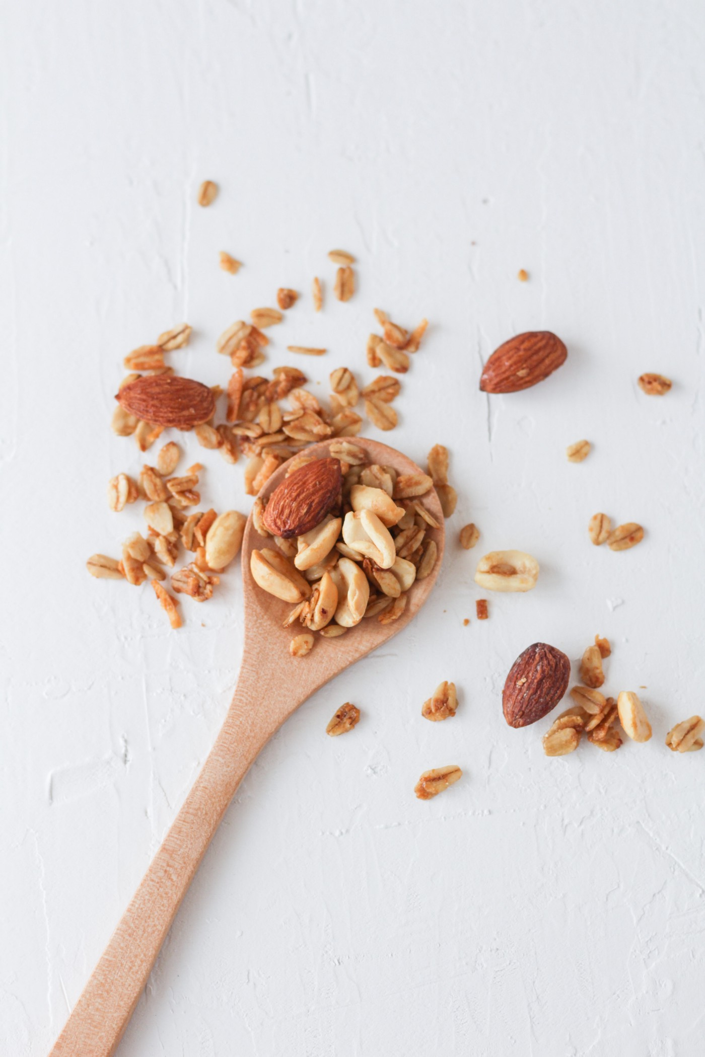 a wooden spoon on a white table with almonds, peanuts and some oatmeal flakes on the spoon and sprinkled on the table around the spoon