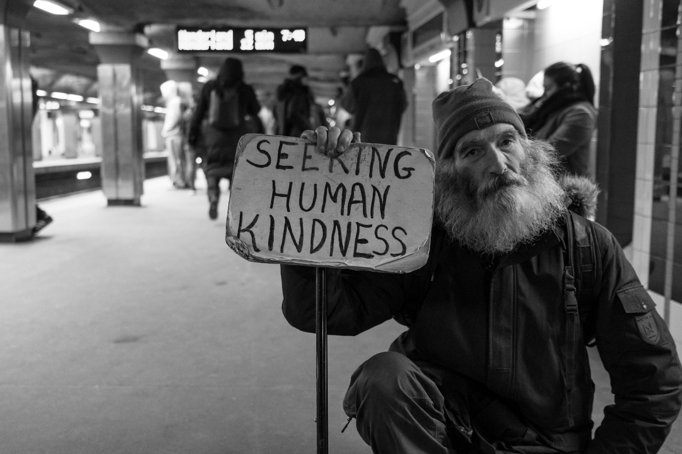 """A bearded man wearing a wool hat and dark jacket on a subway platform, holding a sign that says """"Seeking Human Kindness"""""""