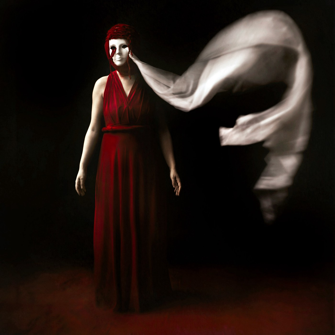 A woman stands in a dark room in a red dress and red head covering wears a mask with white fabric billowing out of the eye hole.