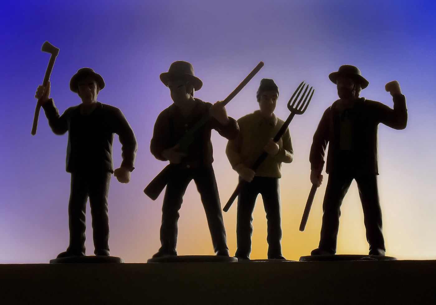Four men, perhaps farmers, make angry gestures while holding an axe, rifle, pitchfork and stick.