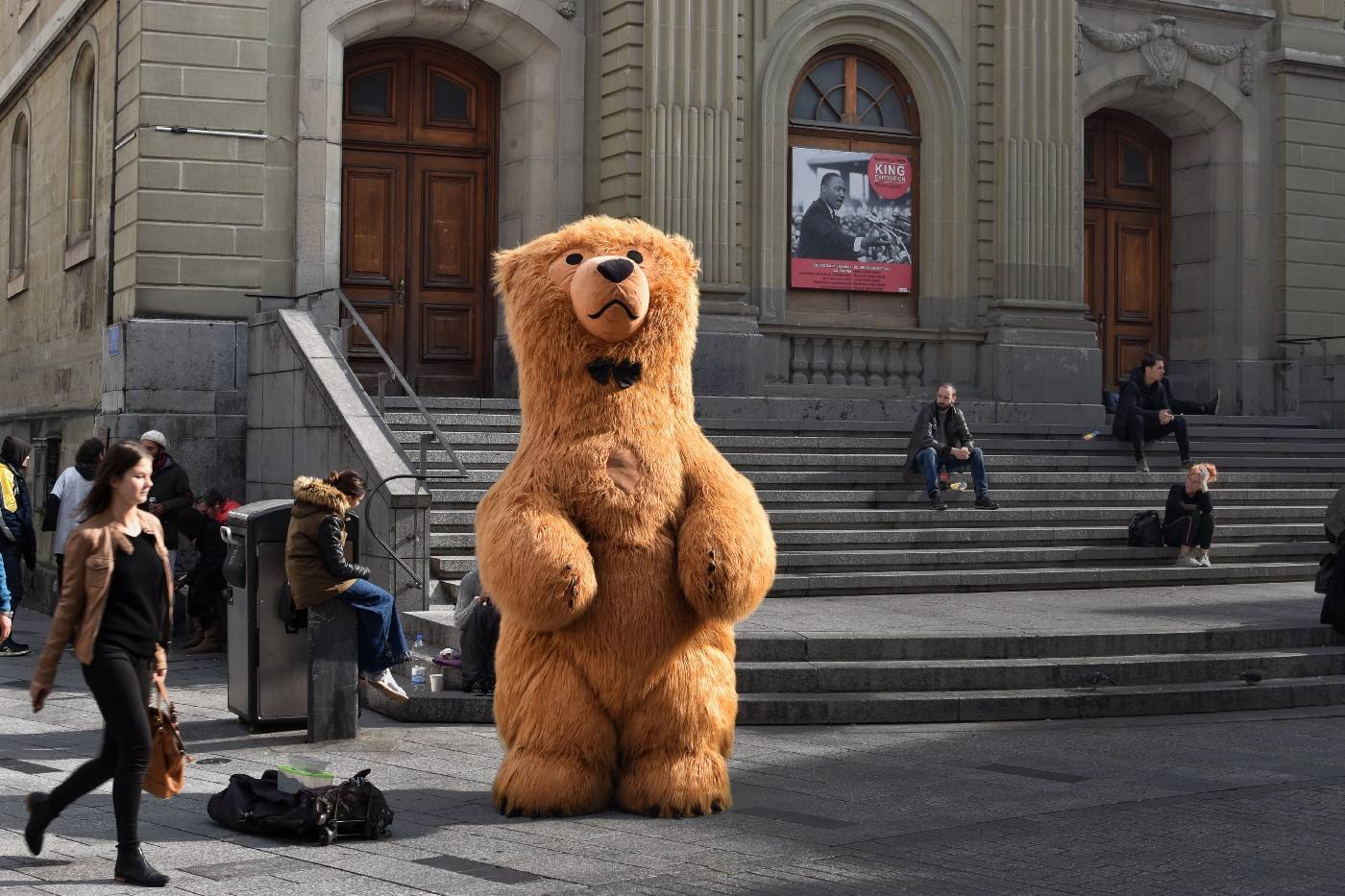 A bear mascot standing in front of a building is looking up, with people sitting on stairs in the background