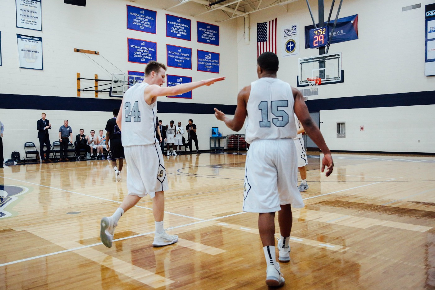 Two basketball players high-fiving each other on a basketball court