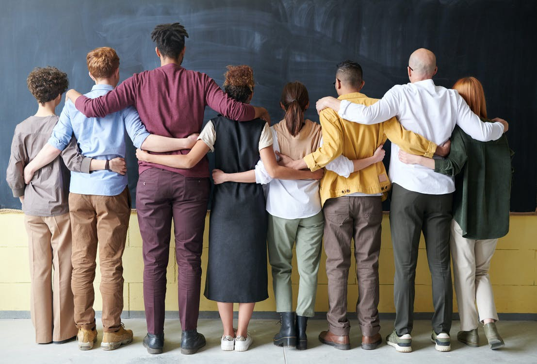 Diverse students put their arms around each other and face a blackboard. #students #diversity #inclusion #friends #friendship