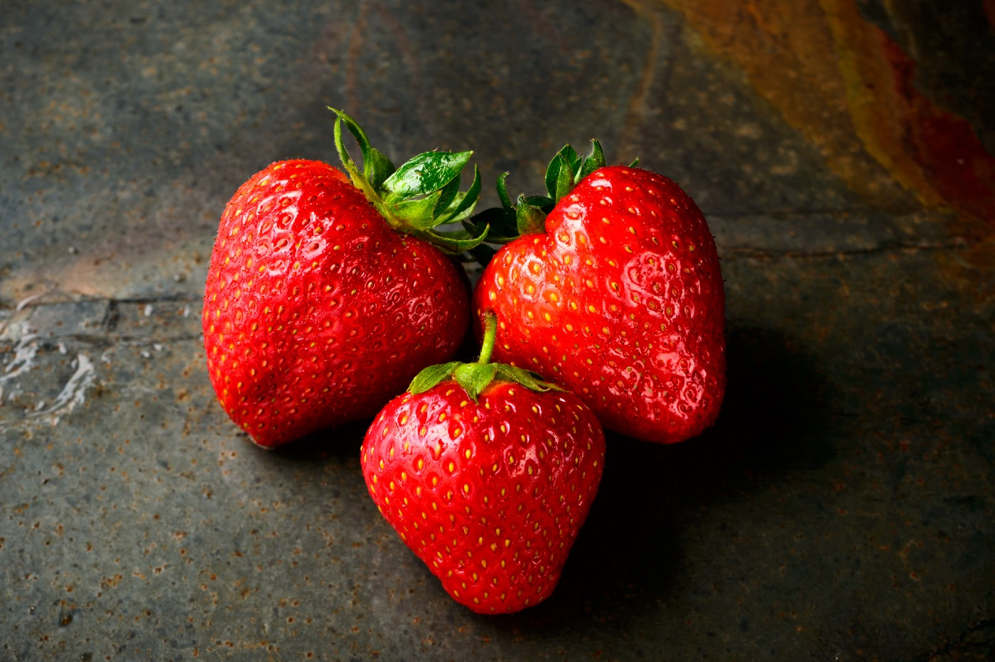 Three strawberries atop a table.
