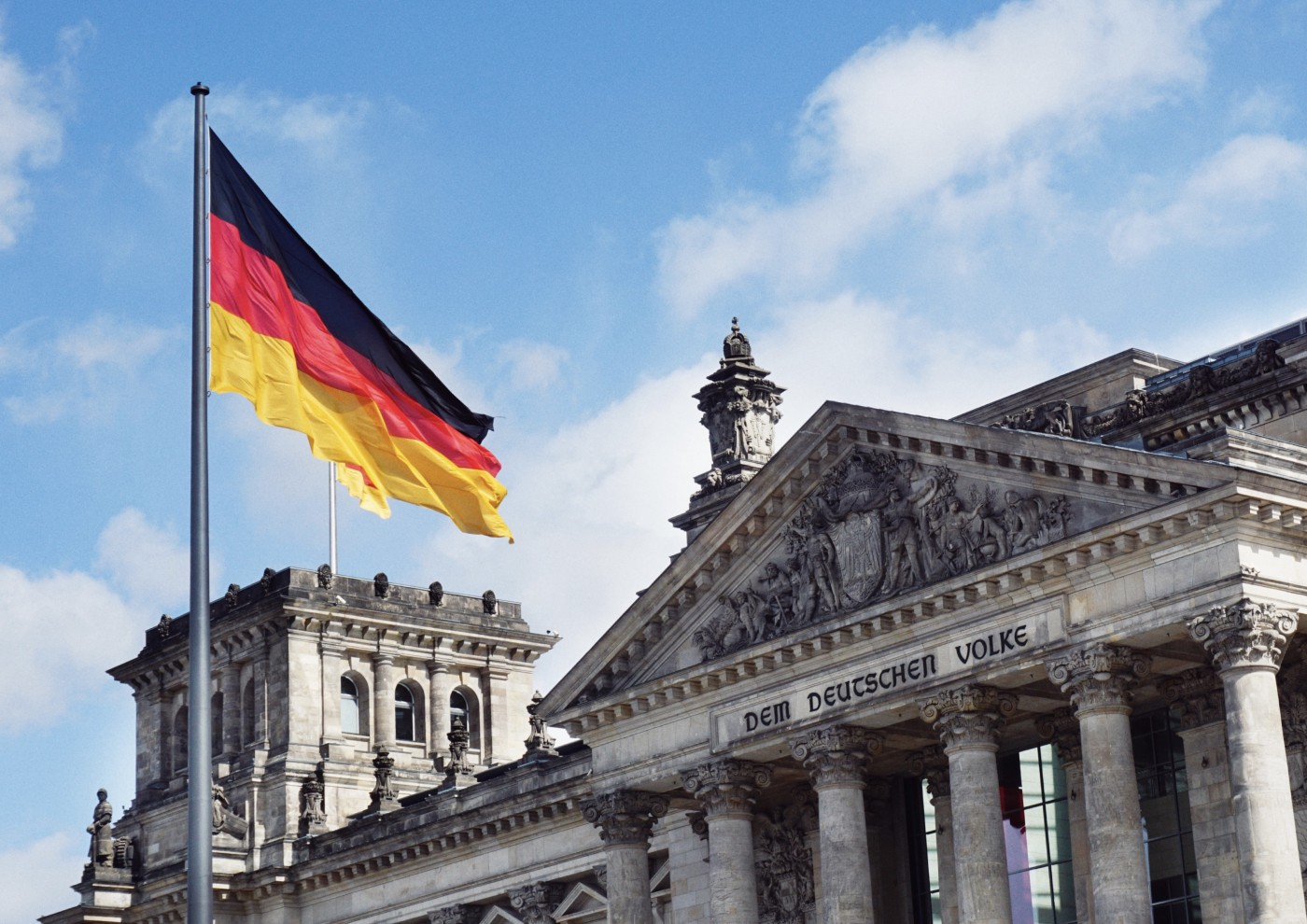 An image of the German Bundestag building with a German flag in front of it.