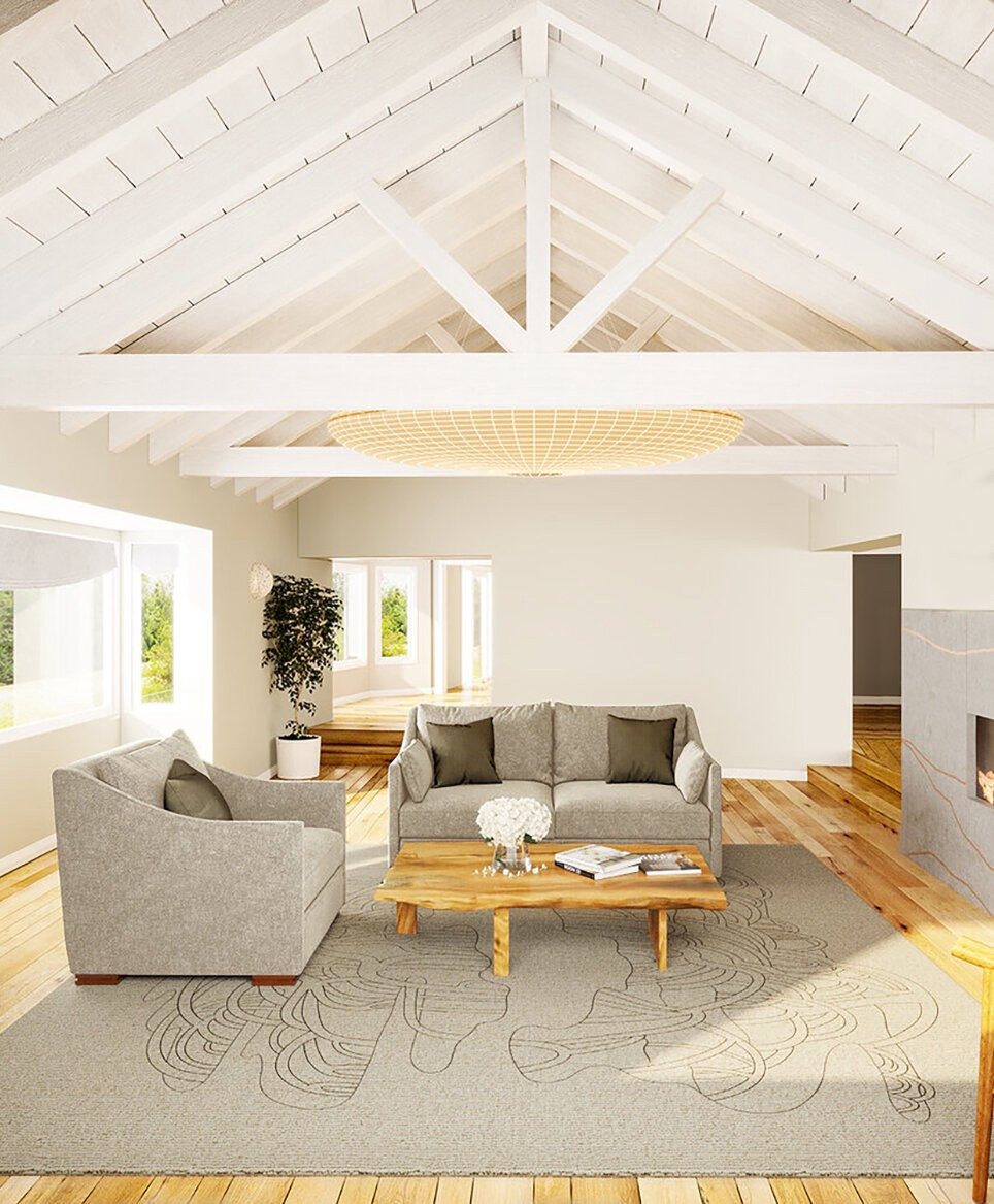 A bright and airy living room with two grey couches, a wooden coffee table, an a frame ceiling and Kale Tree's Mangrove rug in the color Land, which includes a tan base and a brown line drawing of the Mangrove.