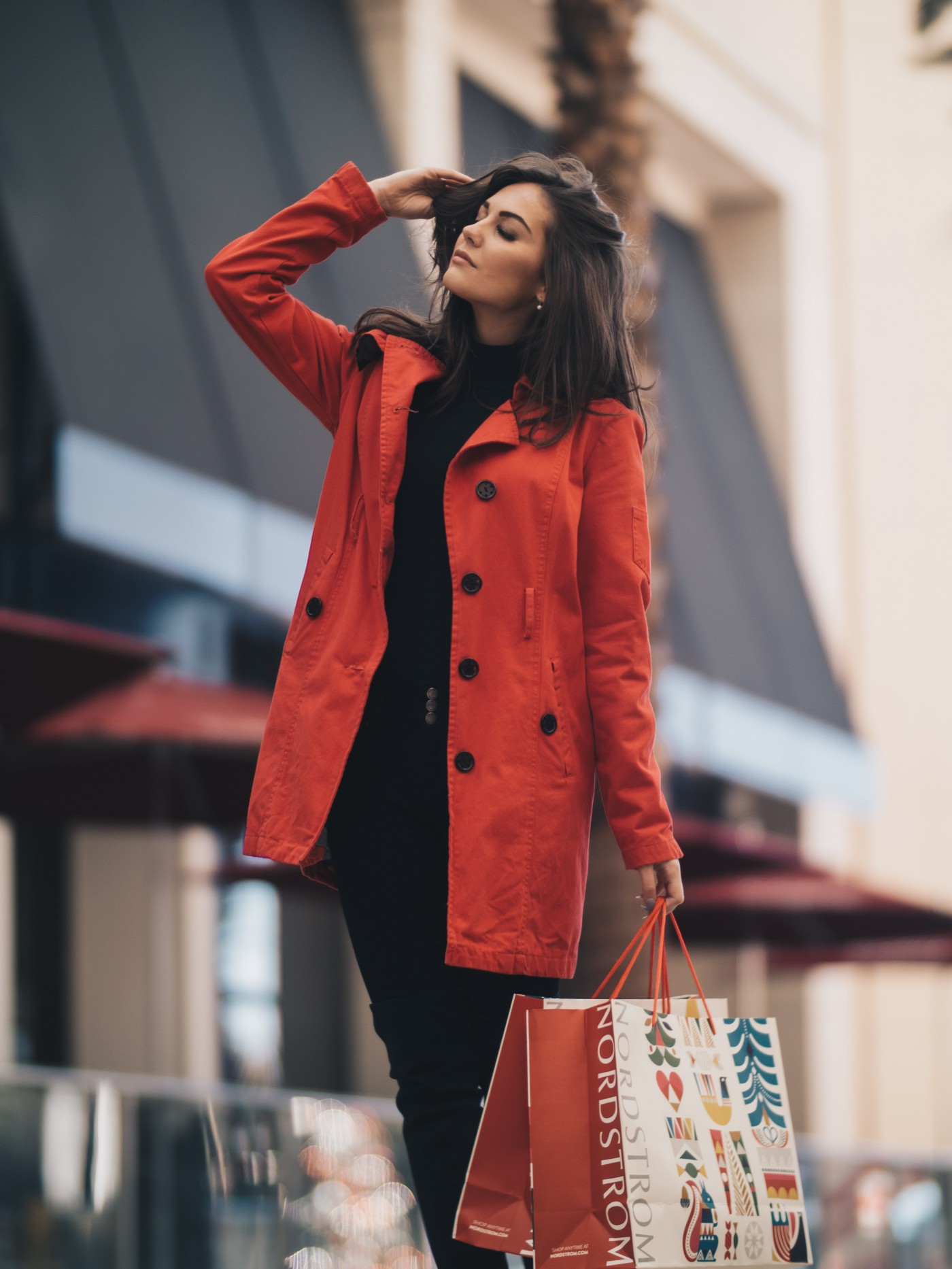 A brunette lovingly caressing her own hair, eyes closed, while walking outside with a hand full of shopping bags from Nordstrom's.