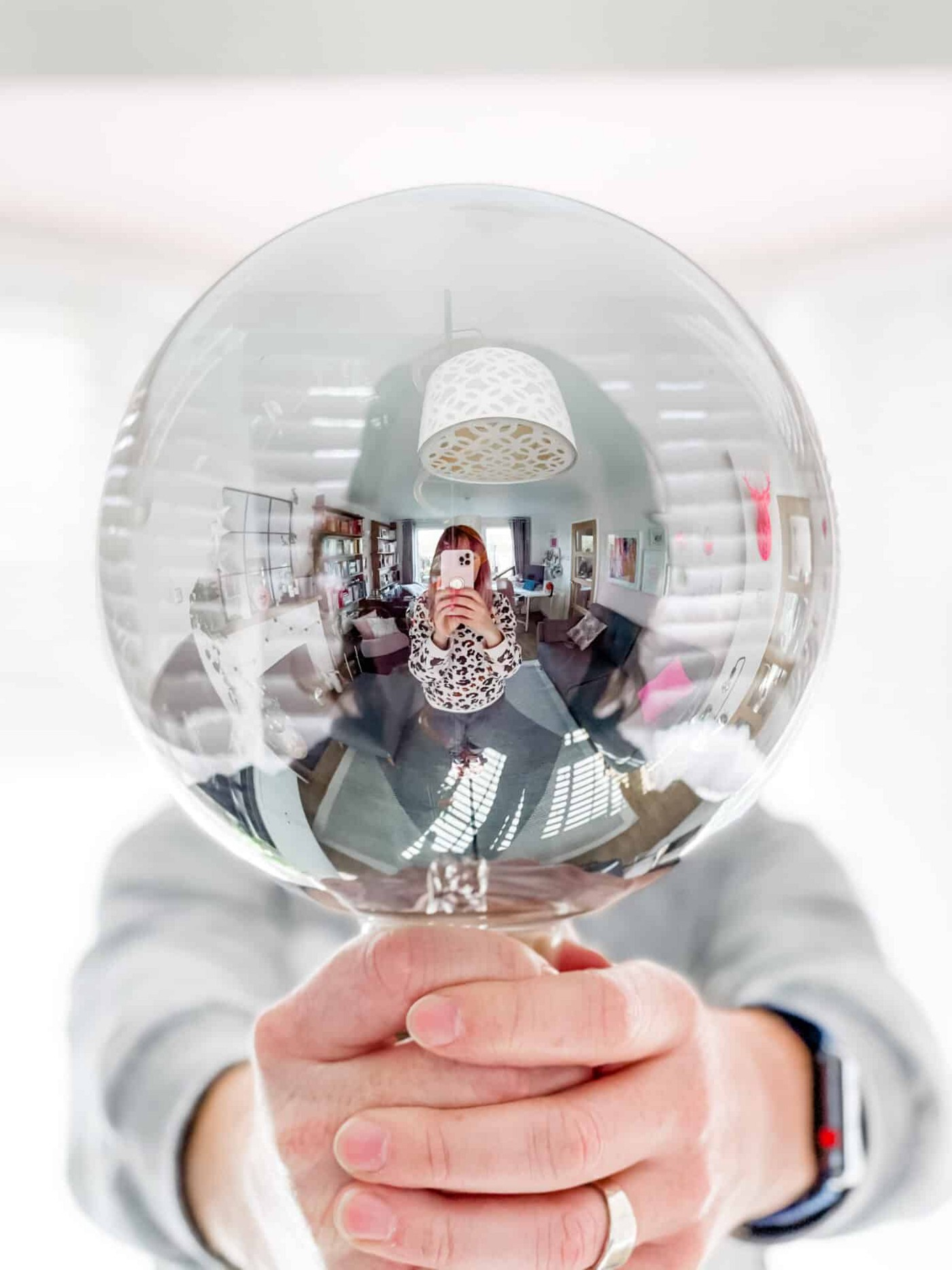 A man holds up a giant LED bulb as a woman takes a picture, you can see the reflection of a lounge in the bulb