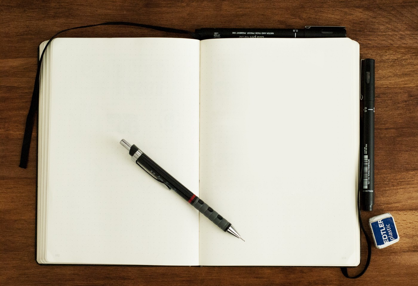 A blank journal laying open on a wood surface with a pen resting on top of the pages.