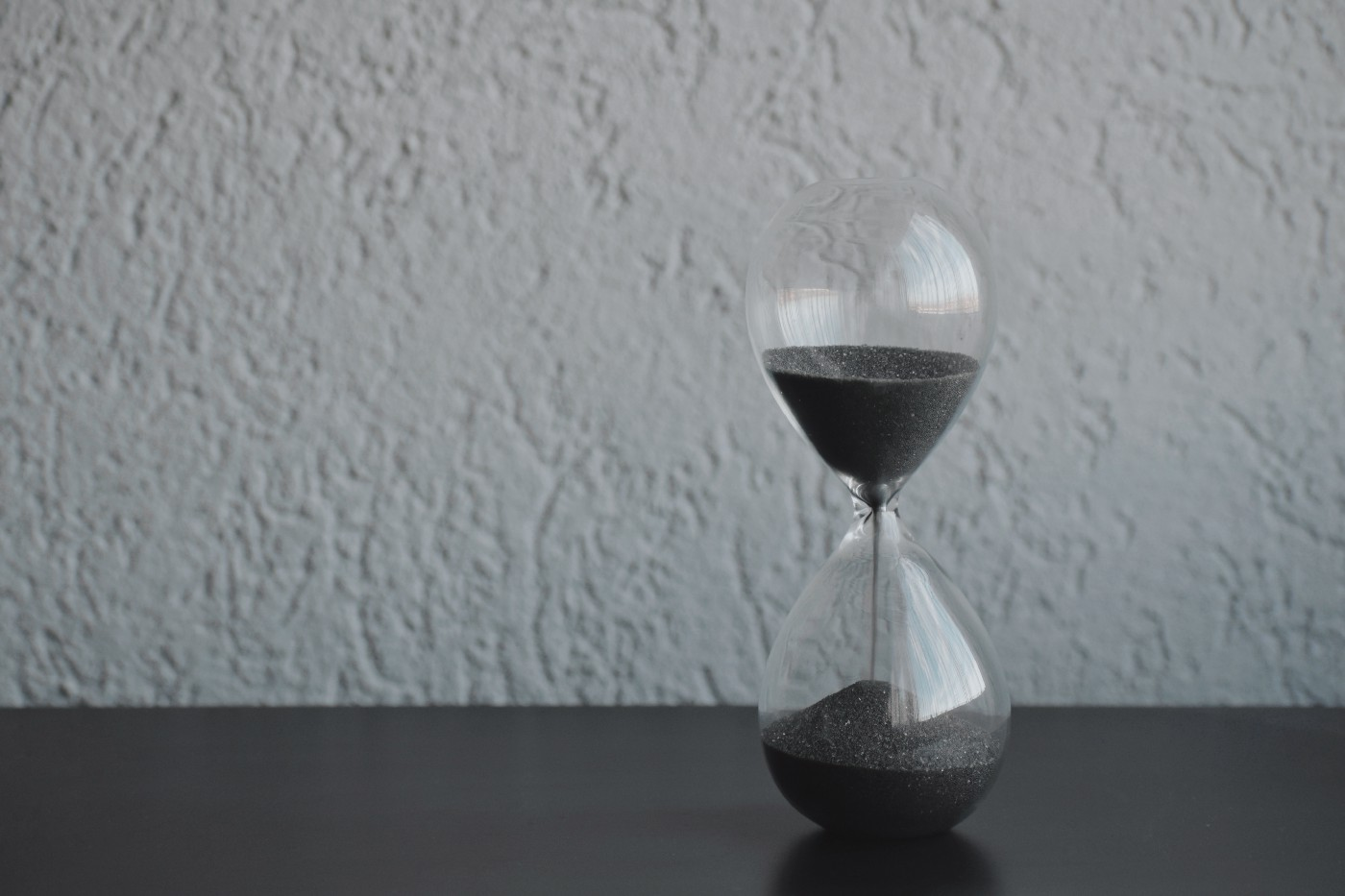 An hourglass on a black surface, sand falling.