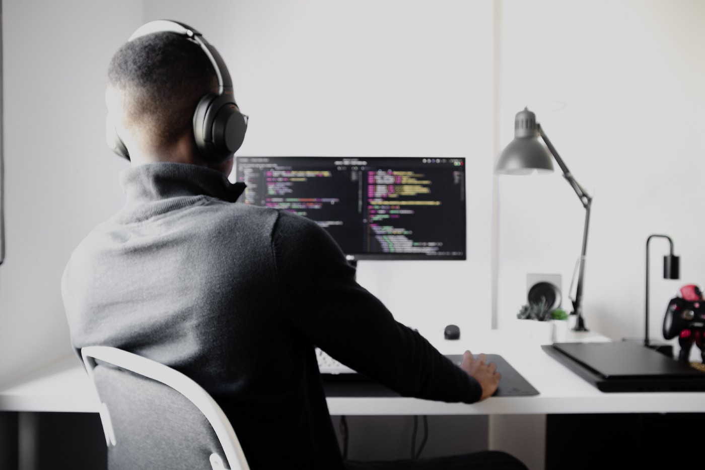 Man in black long sleeve shirt wearing black headphones, sitting on a chair, looking at a computer screen with code editor open