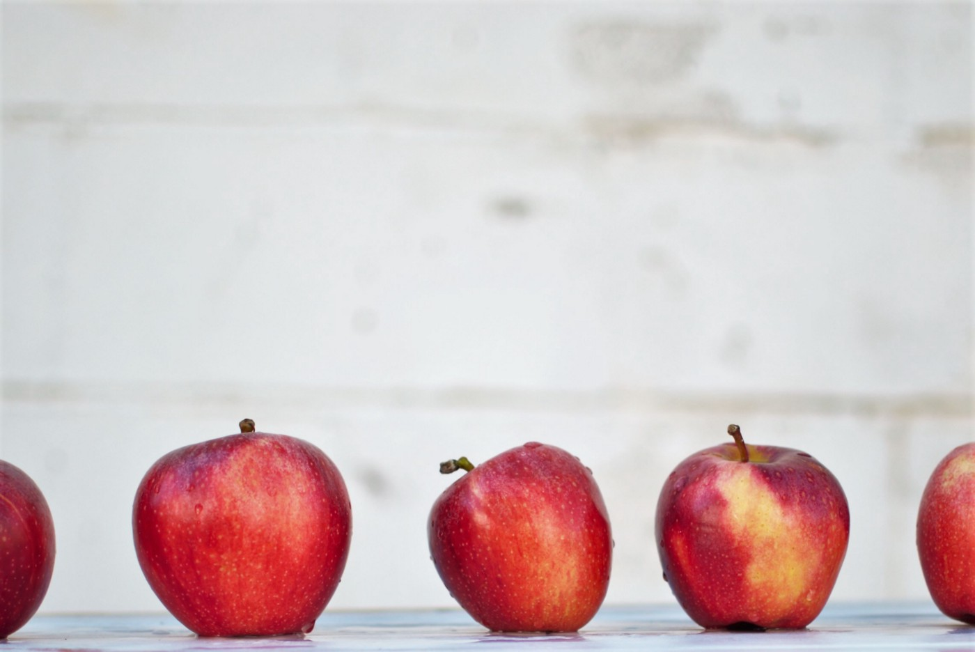 A lineup of red apples differing slightly in shade and size.
