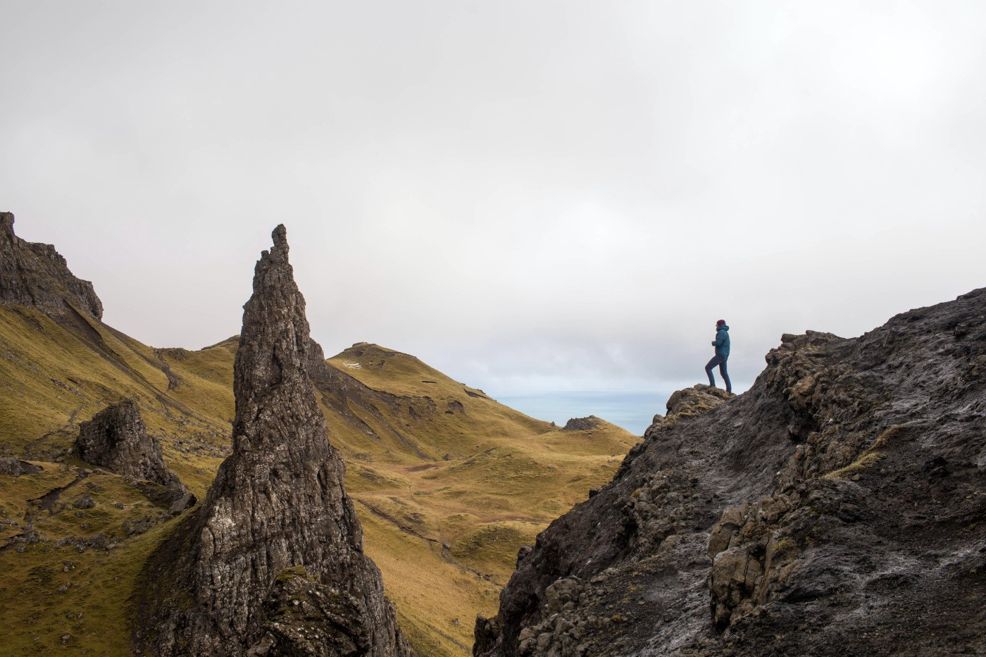 A person standing on top of a rock formation, advancing towards an even higher peak.