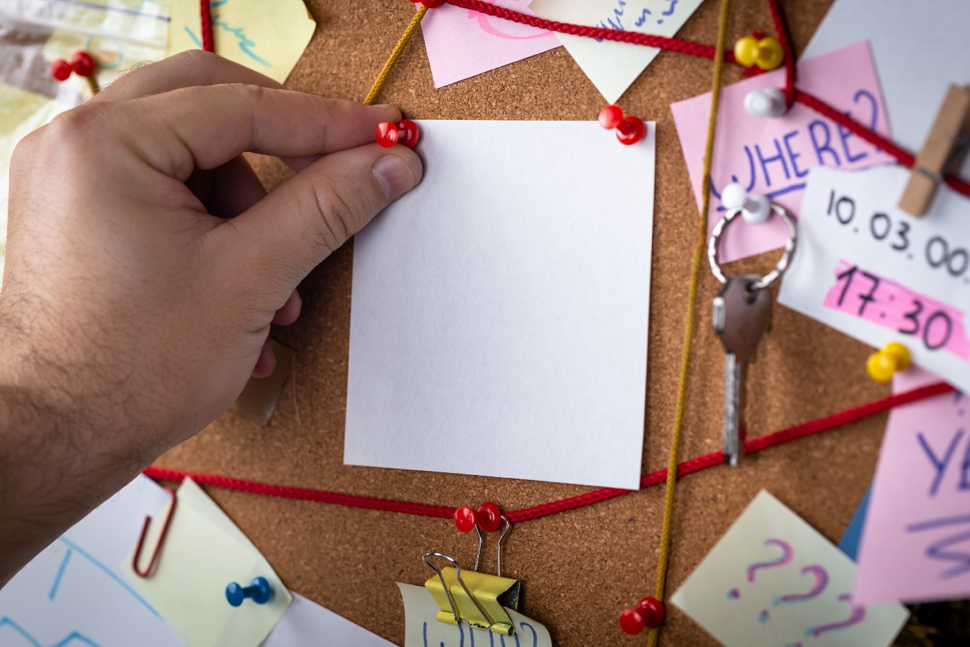 corkboard, evidence board with red yarn showing associations between evidence