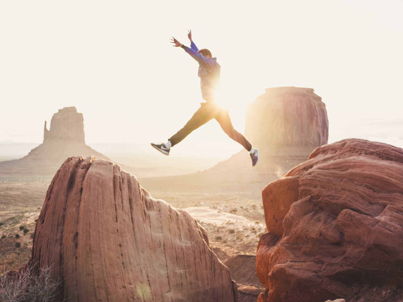 Person wearing Nike sneakers with raised arms jumping from rock to rock in rocky desert. Sunset in the background.
