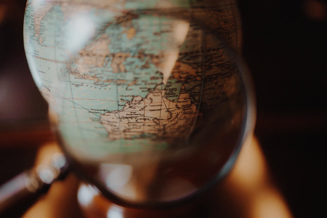 Image: Magnifying glass on a globe.