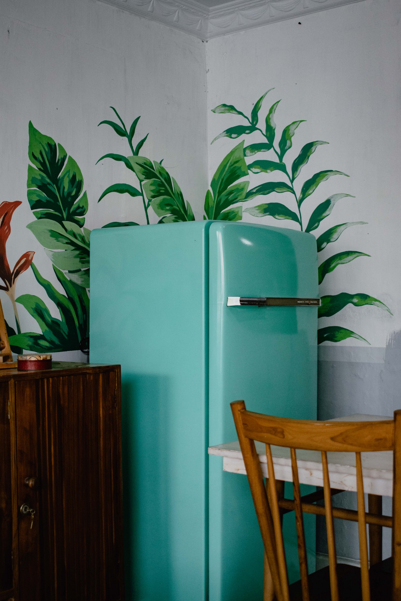 teal green refridgerator in a kitchen. A chair is in front of it, and painted leaves are behind it on the white wall.