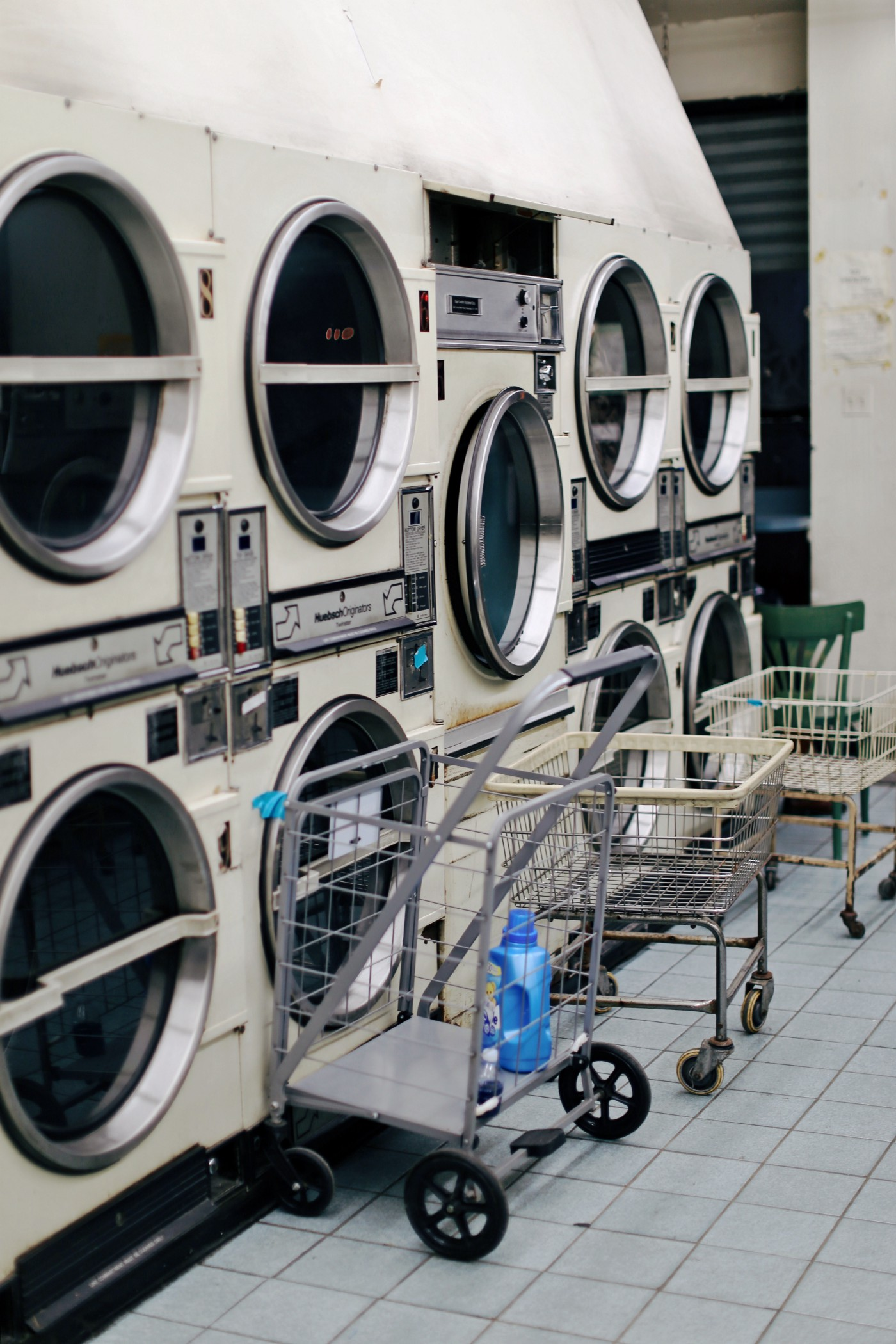 An old coin laundromat with three wire laundry carts