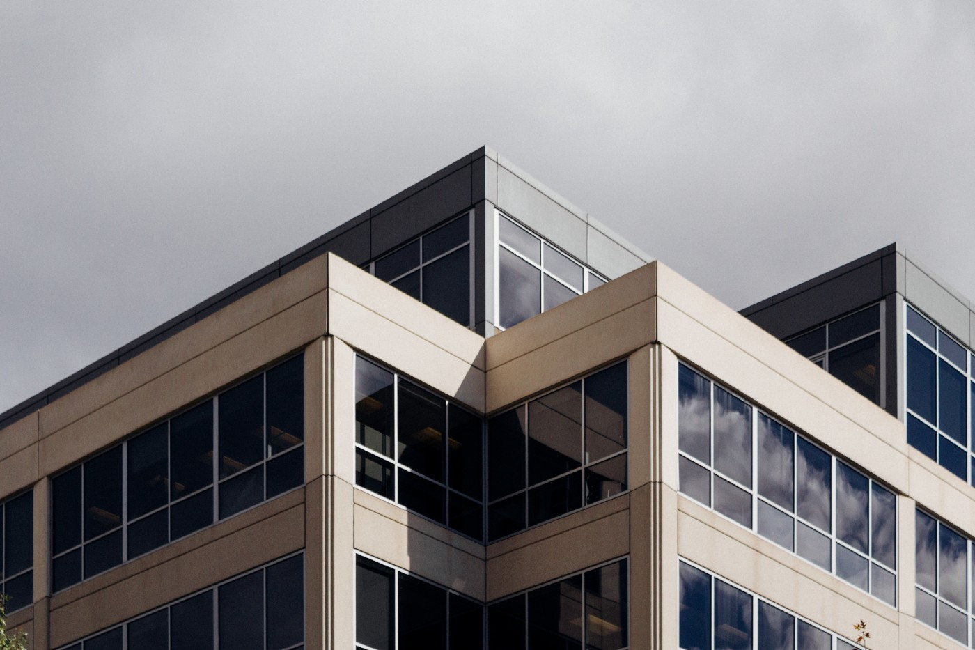 Angular modern building with many windows against a grey sky