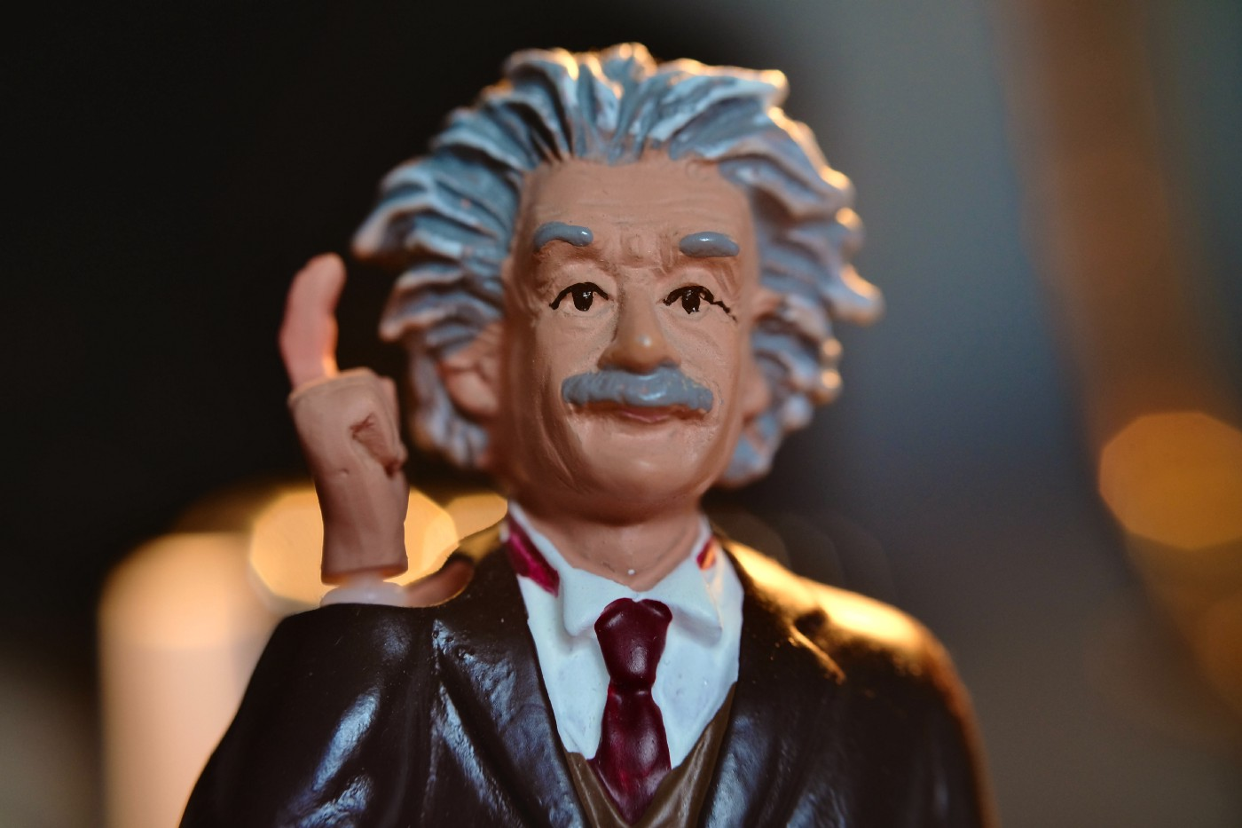 A close-up of a realistically painted model of renowned scientist, Albert Einstein, wearing a smart dark brown blazer, white shirt nd red tie. The model is posing with its right arm raised and index finger pointed towards the sky, as if having a Eureka moment. The models facial expression looks collected and confident, wearing a slight smile as it looks into the distance. The background is blurred but there are a few lights distinguishable.