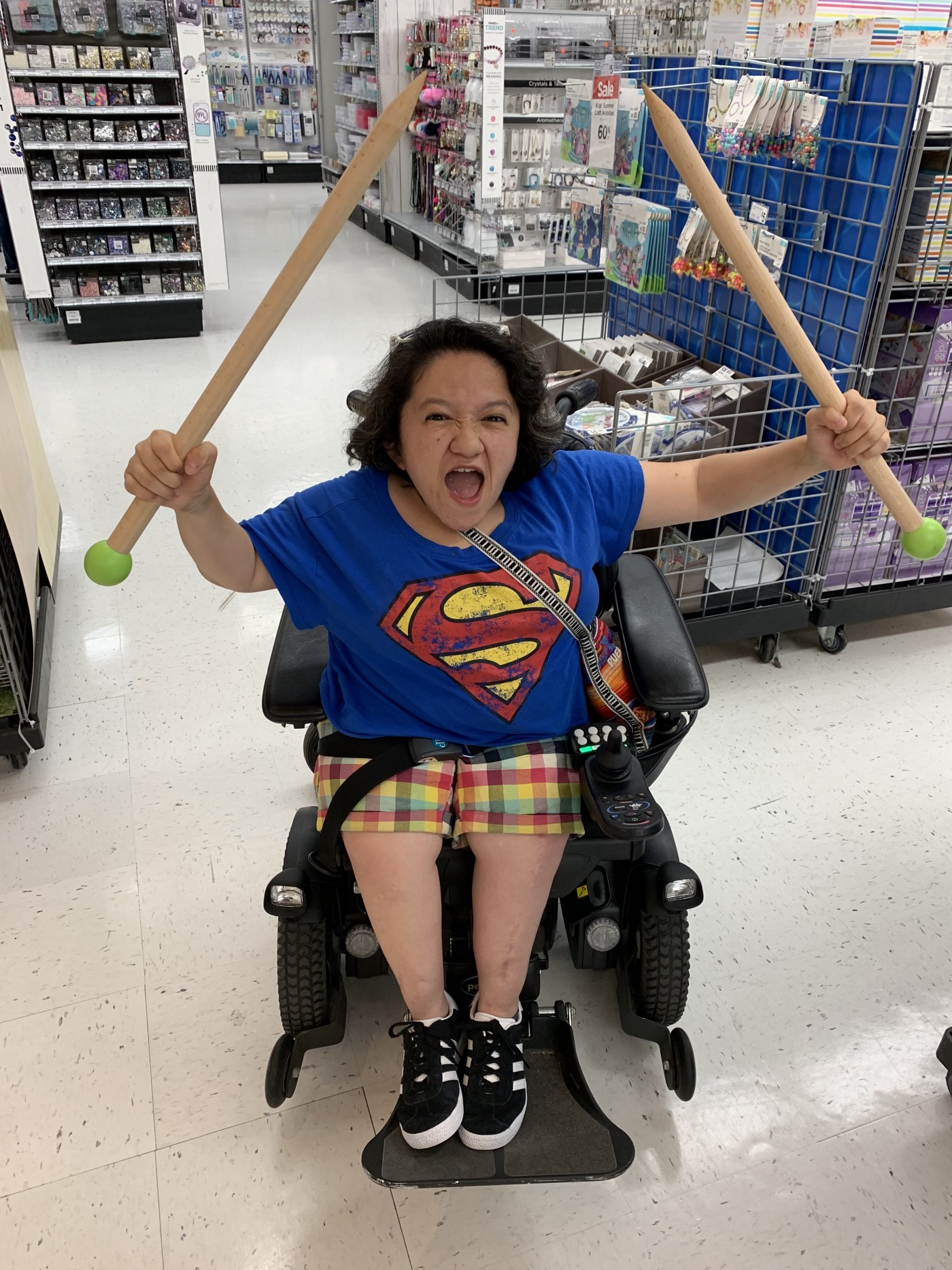 Sandy Ho, an Asian American woman with dark curly hair sits in a black power wheelchair. She is wearing a blue tshirt.