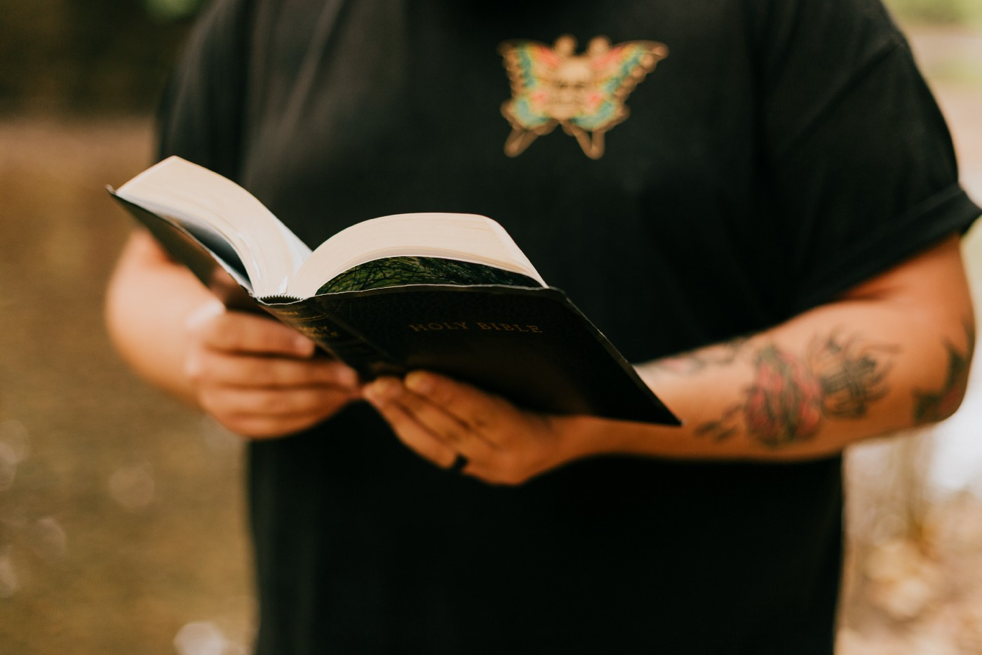 man standing while reading a black book