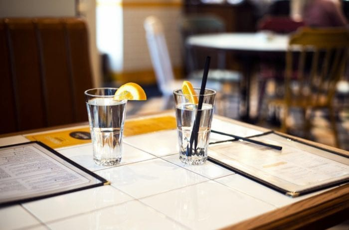 two water glasses and menus on a table