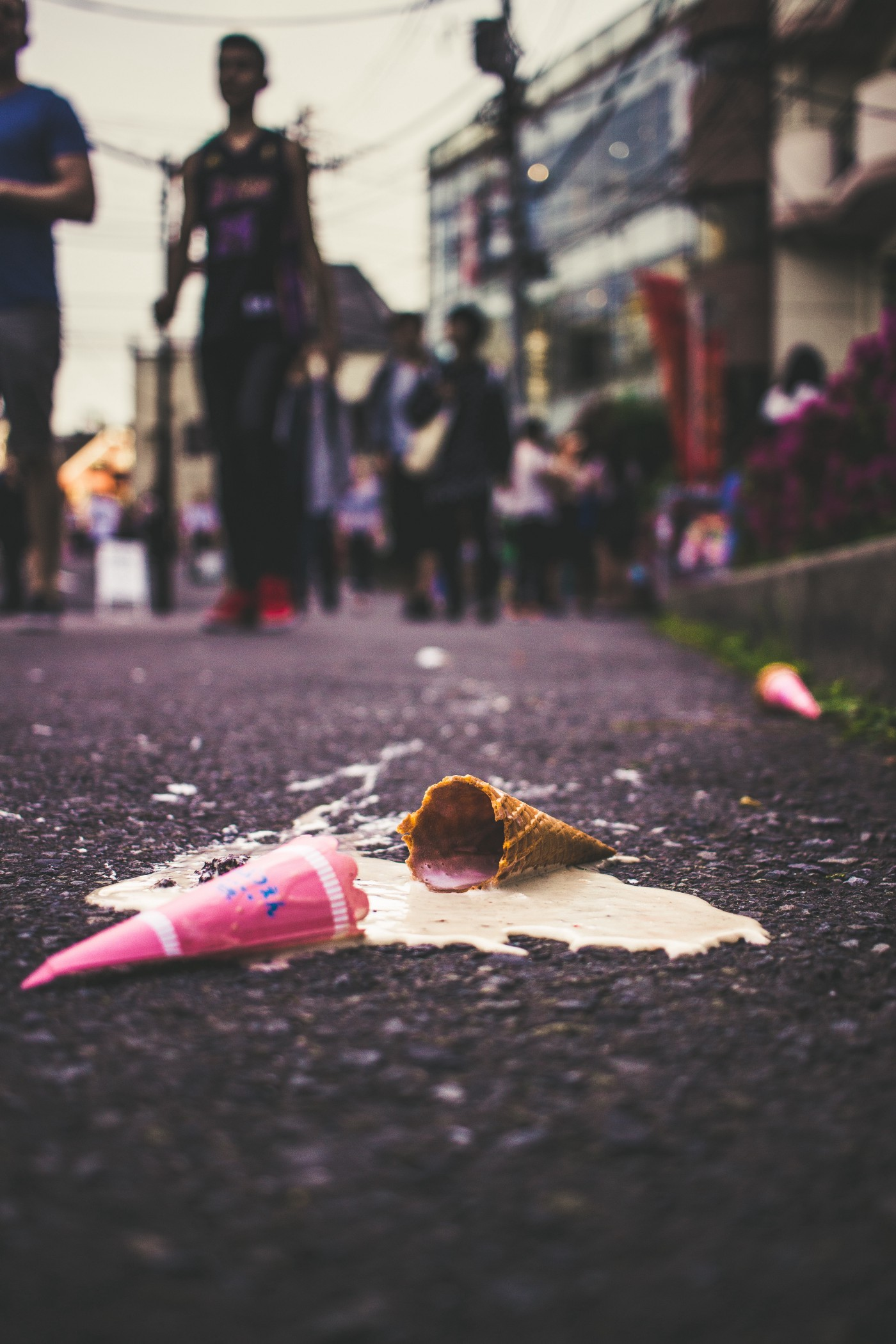 ice cream cone on the street in a puddle of melted ice cream