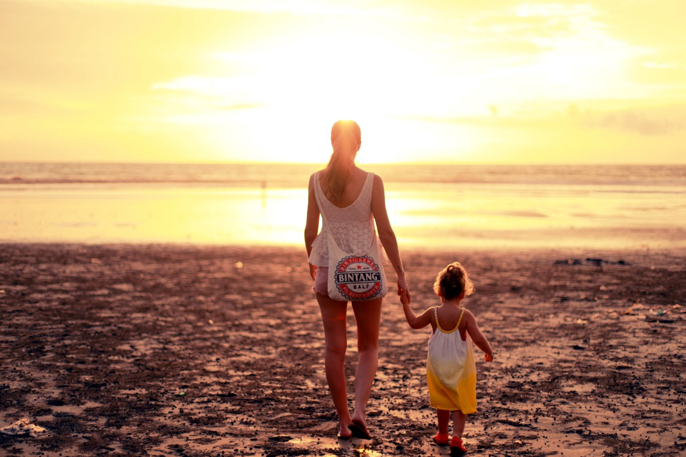 A single mother walks on the beach towards a sunset.