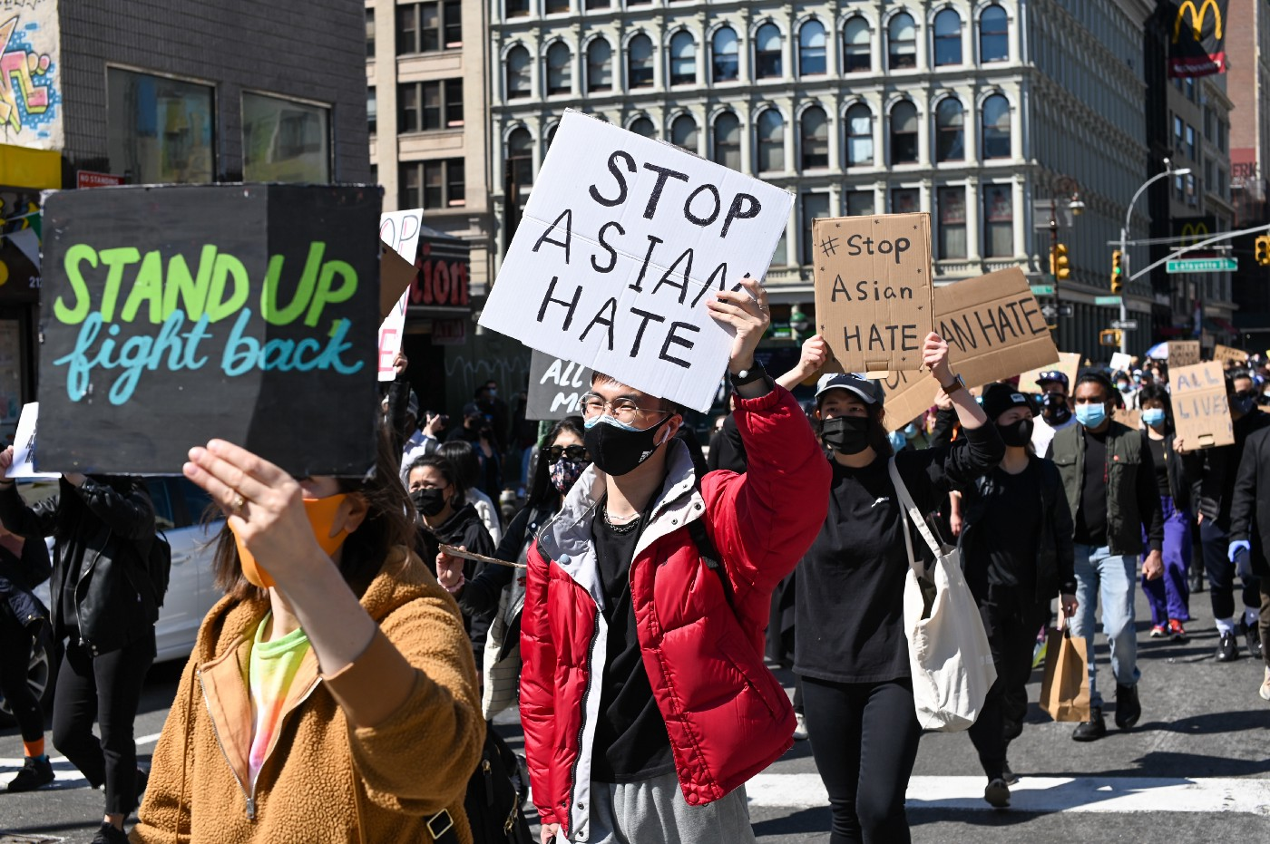 "People at a protest holding signs that say ""stop Asian hate"""