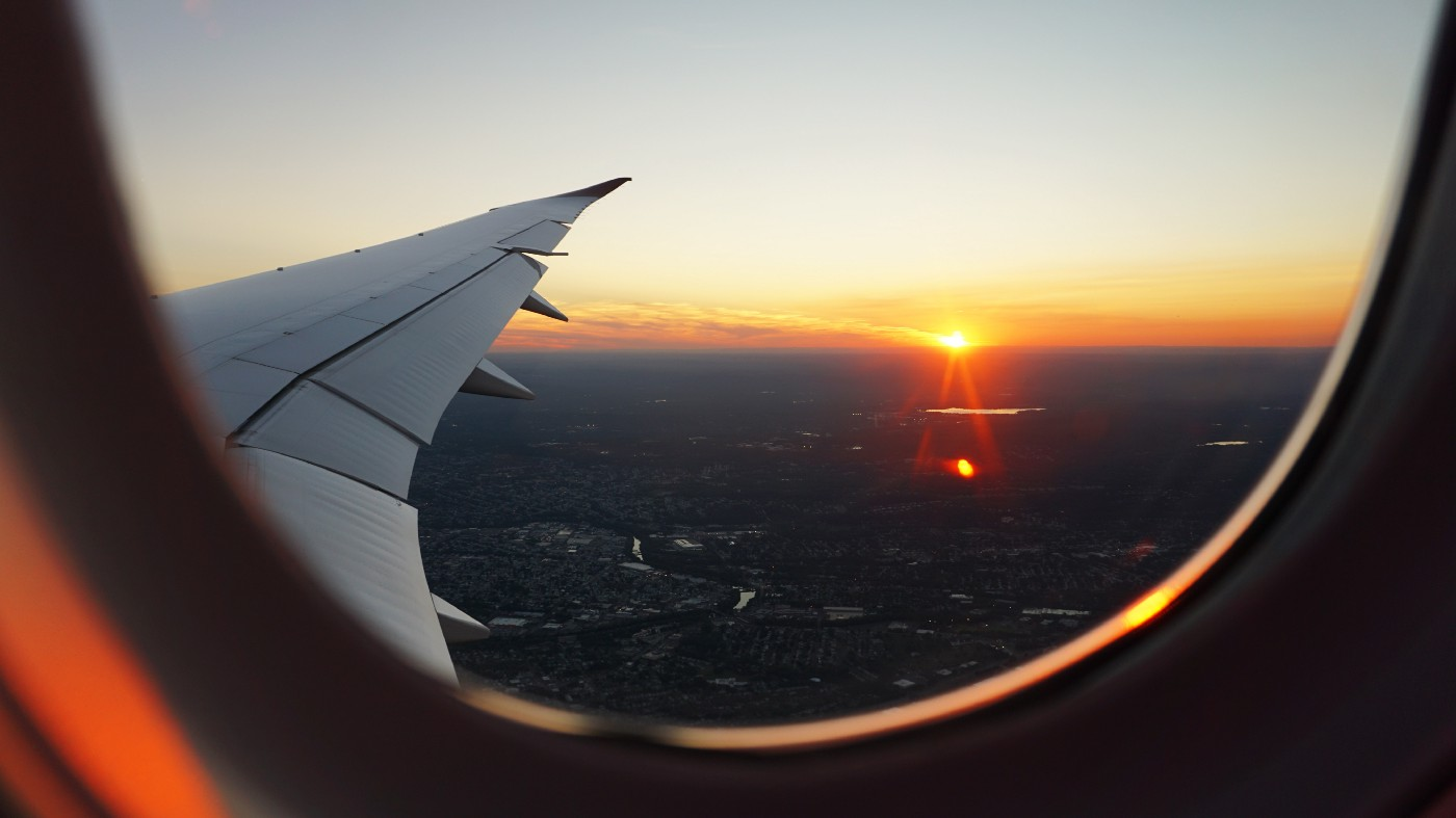 View from an airplane window at sunset, overlooking the right-side plane wing.