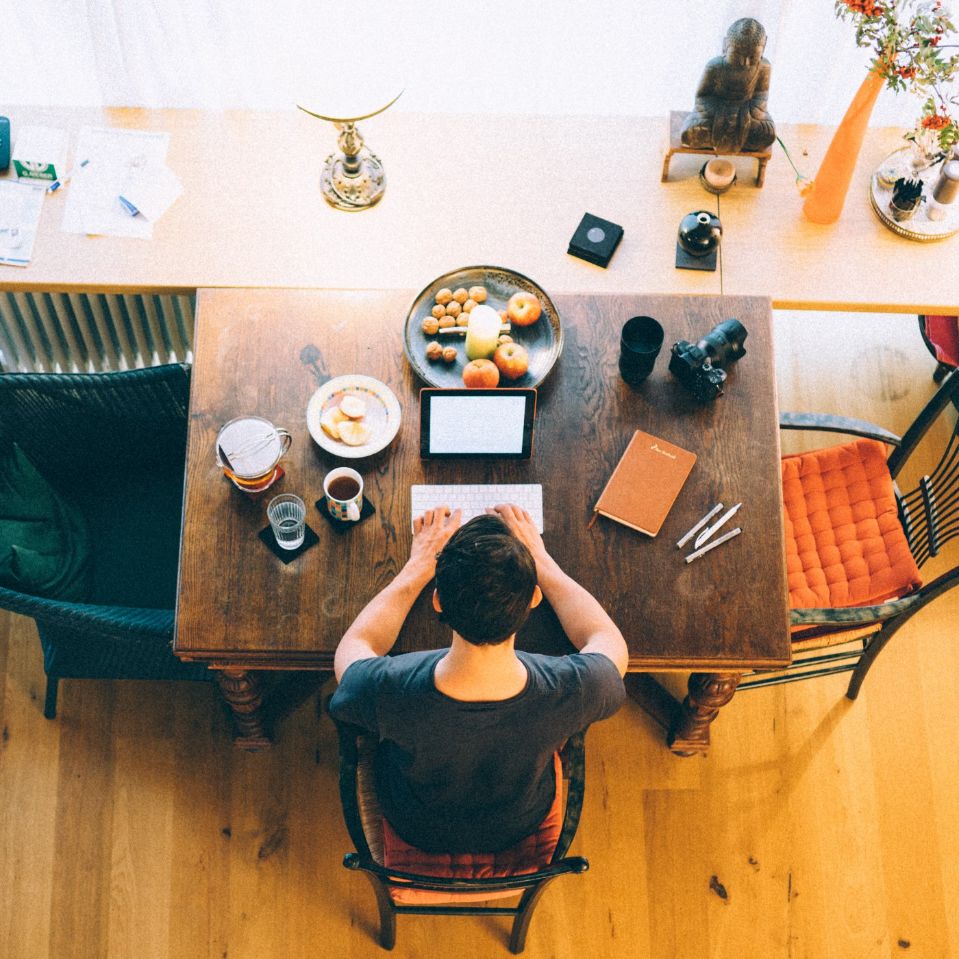Man types on an iPad on his desk while surrounded by food.