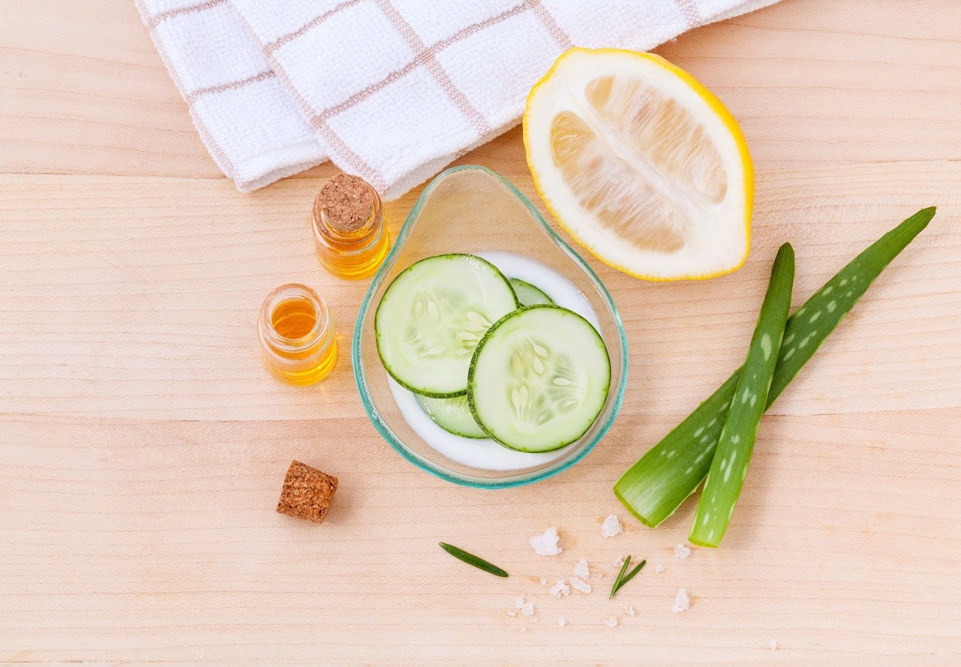 Skincare items with lemon cucumber slices and aloe vera with face oils