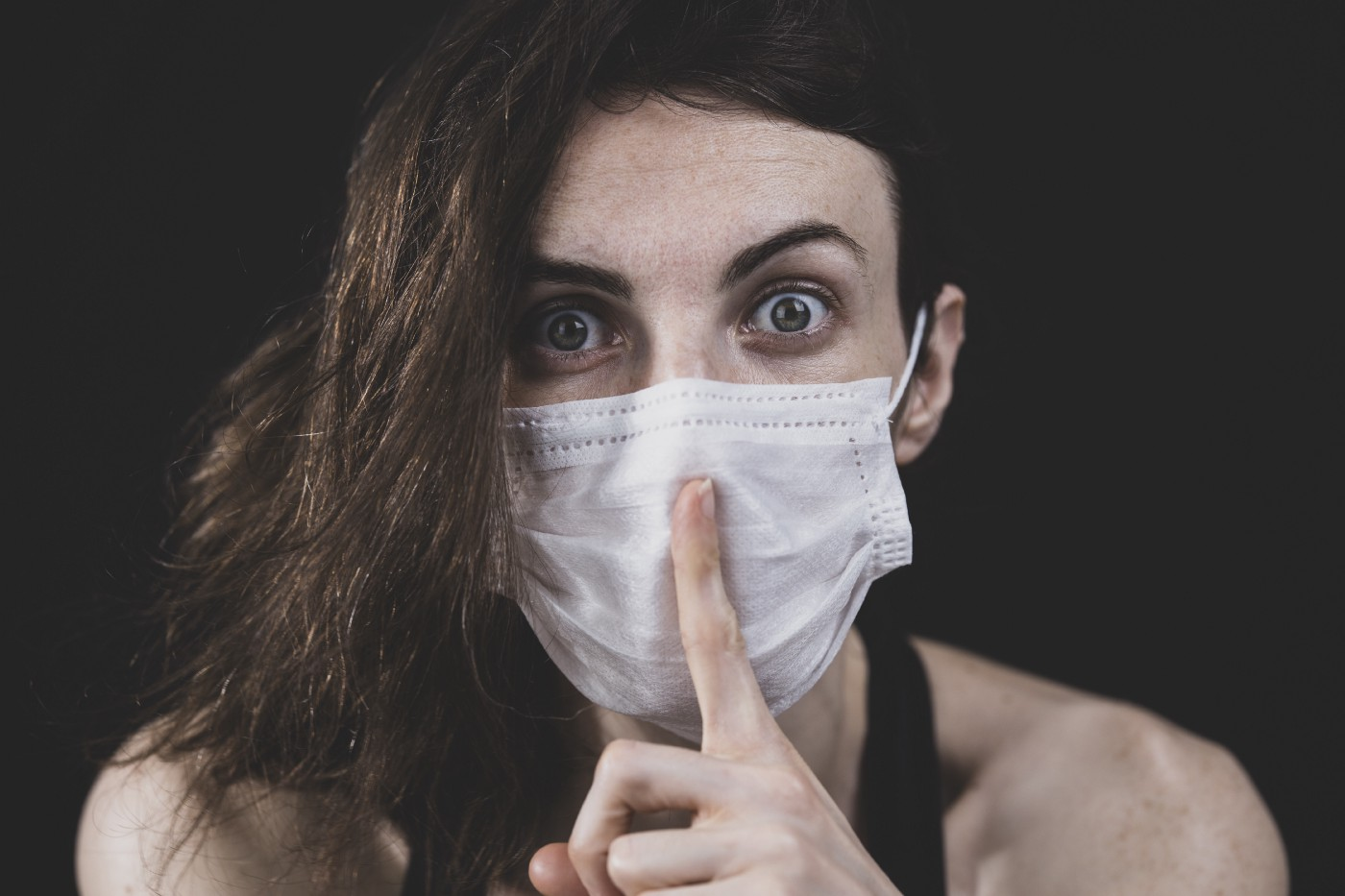 Woman wearing a face mask and holding a finger to her lips as if keeping a secret.