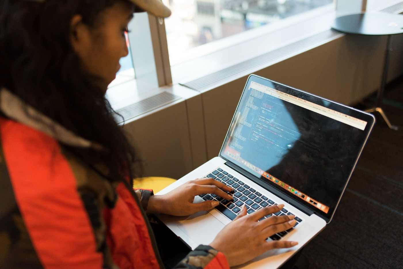 Woman working on code on a laptop