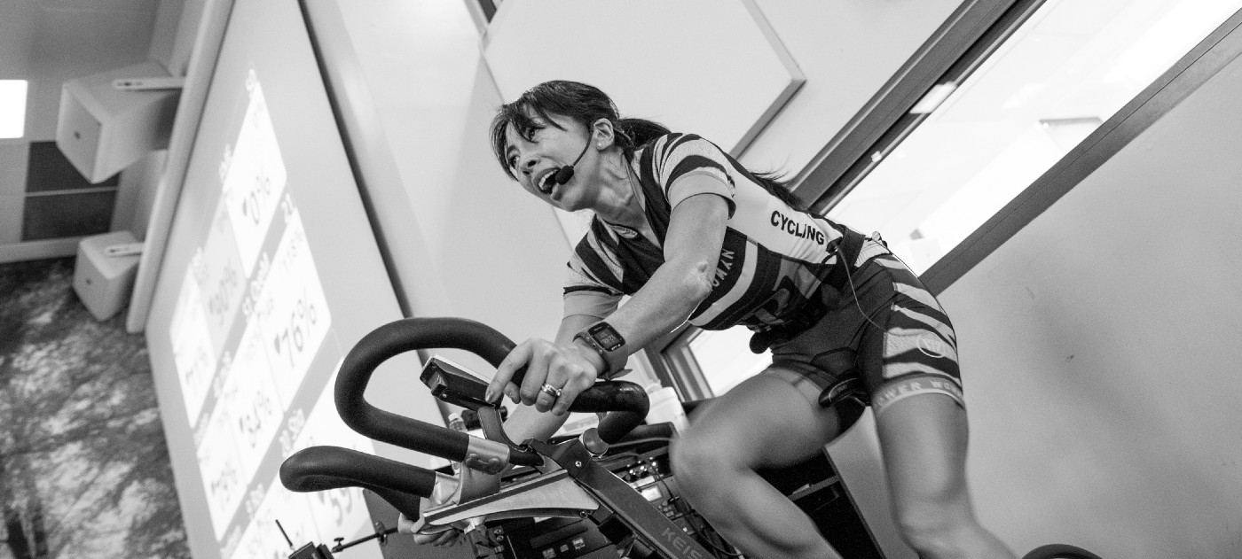 Female indoor cycling instructor on bike