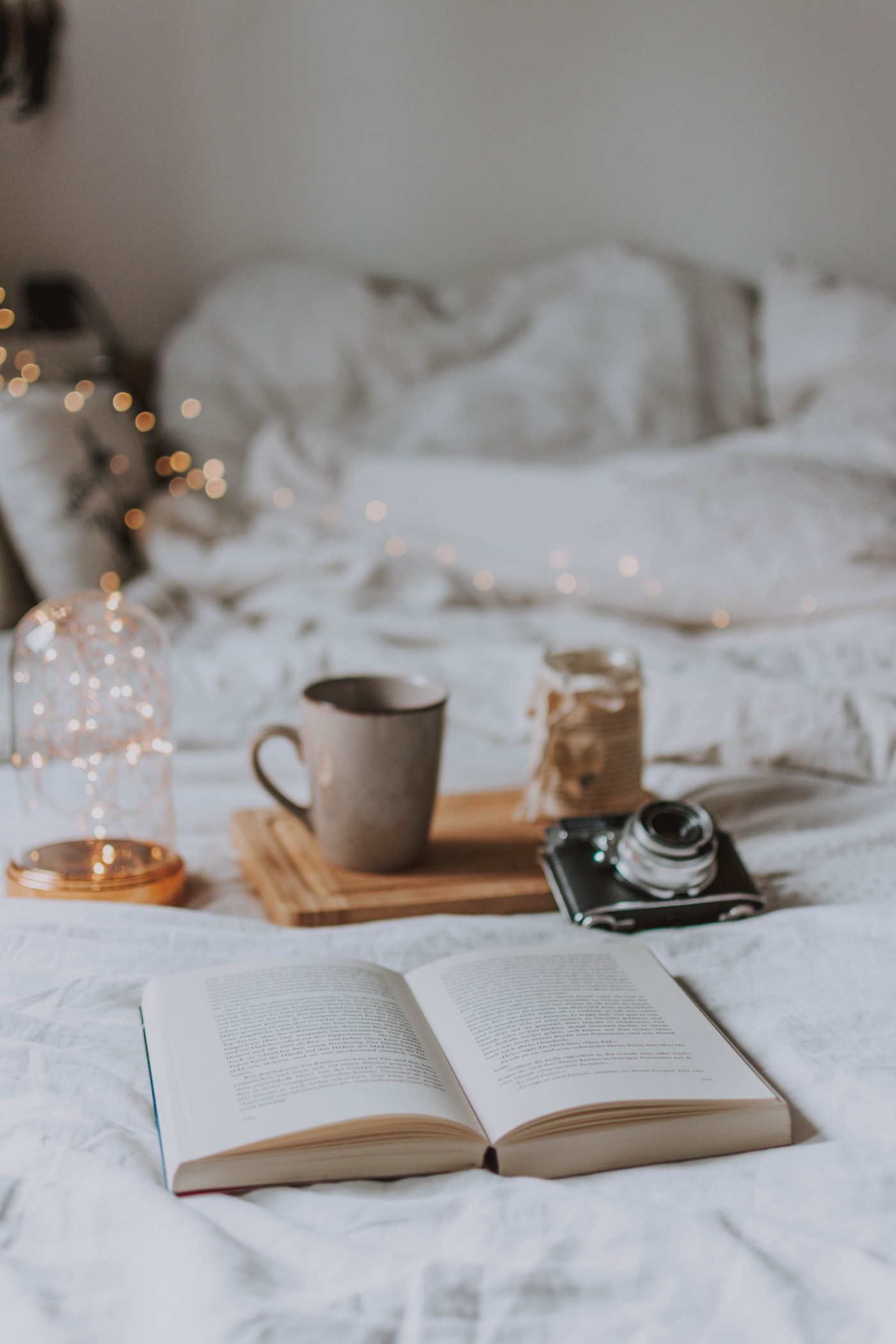 Book, open-faced on a bed with various items. A glittery light creates a magical feel next to a coffee mug on a tray and vintage camera.