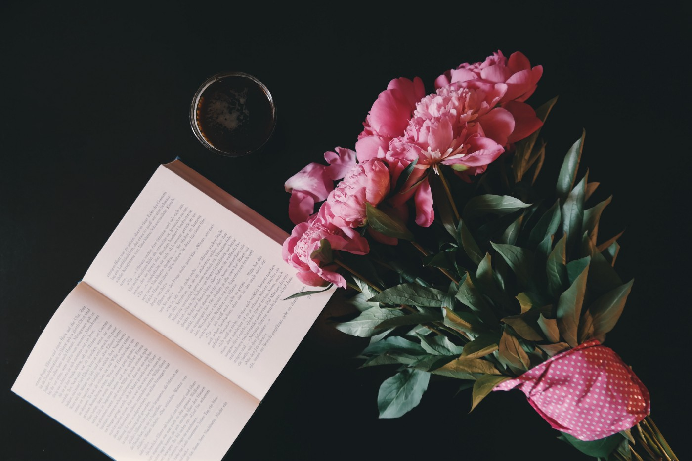 An open book on a table, with a cup of coffee and a bouquet of flowers.