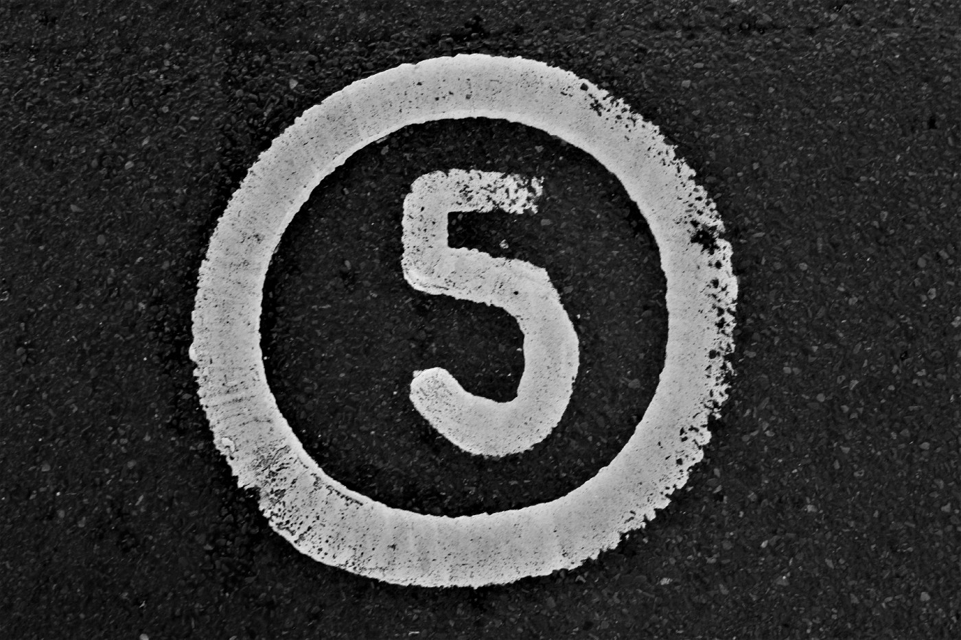 A simple image of the number five in white paint against a black background. The five is encircled with more white paint.
