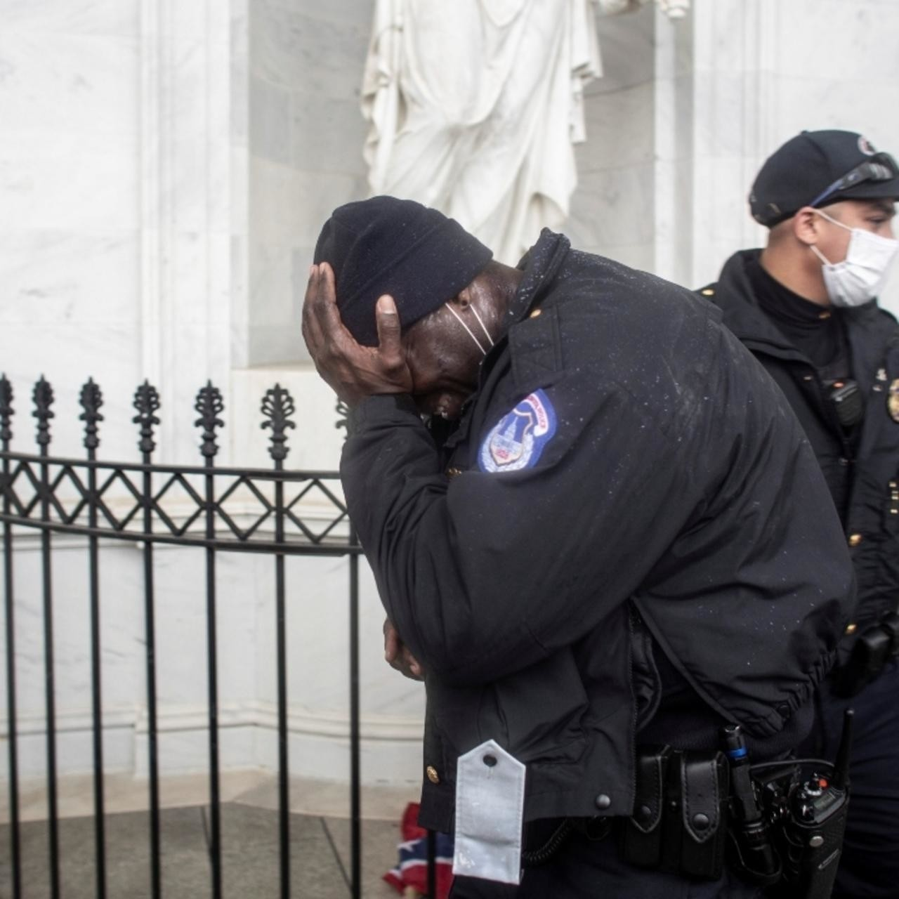 police officers outside the Capitol on January 6, one holds his head in his hands