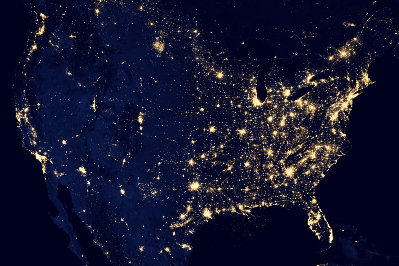 An aerial shot of the United States, showing the most populated areas lit up by lights.