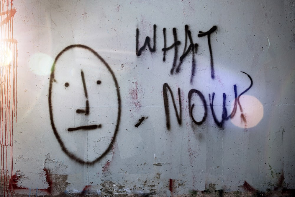 """Wall painting with the words """"What Now?""""—Image by Tim Mossholder—Unsplash"""