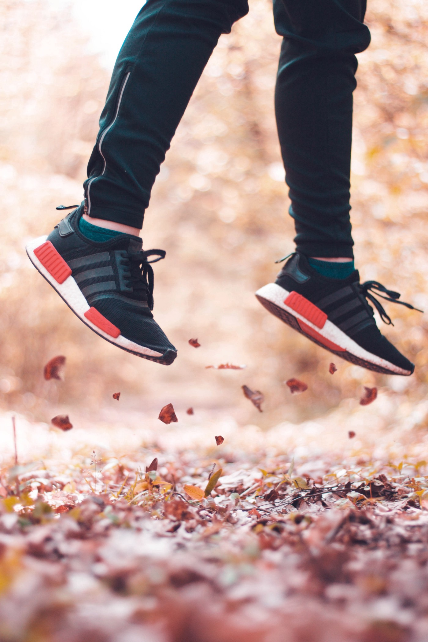 Sneaker-clad feet and lower leg shown jumping up from leaf-strewn ground