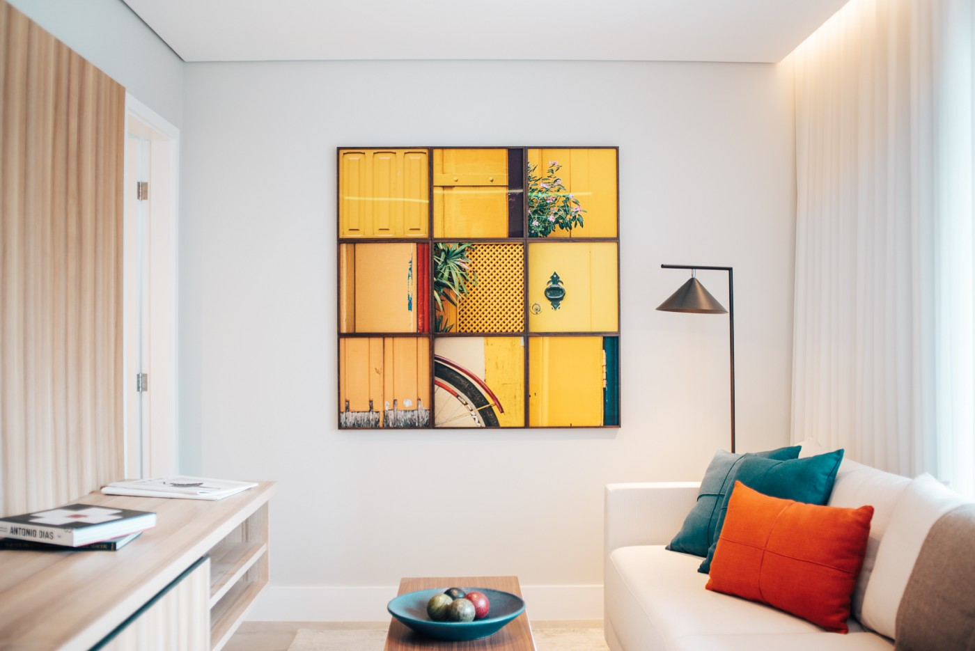 A tidy modern lounge with a colourful artwork on the wall