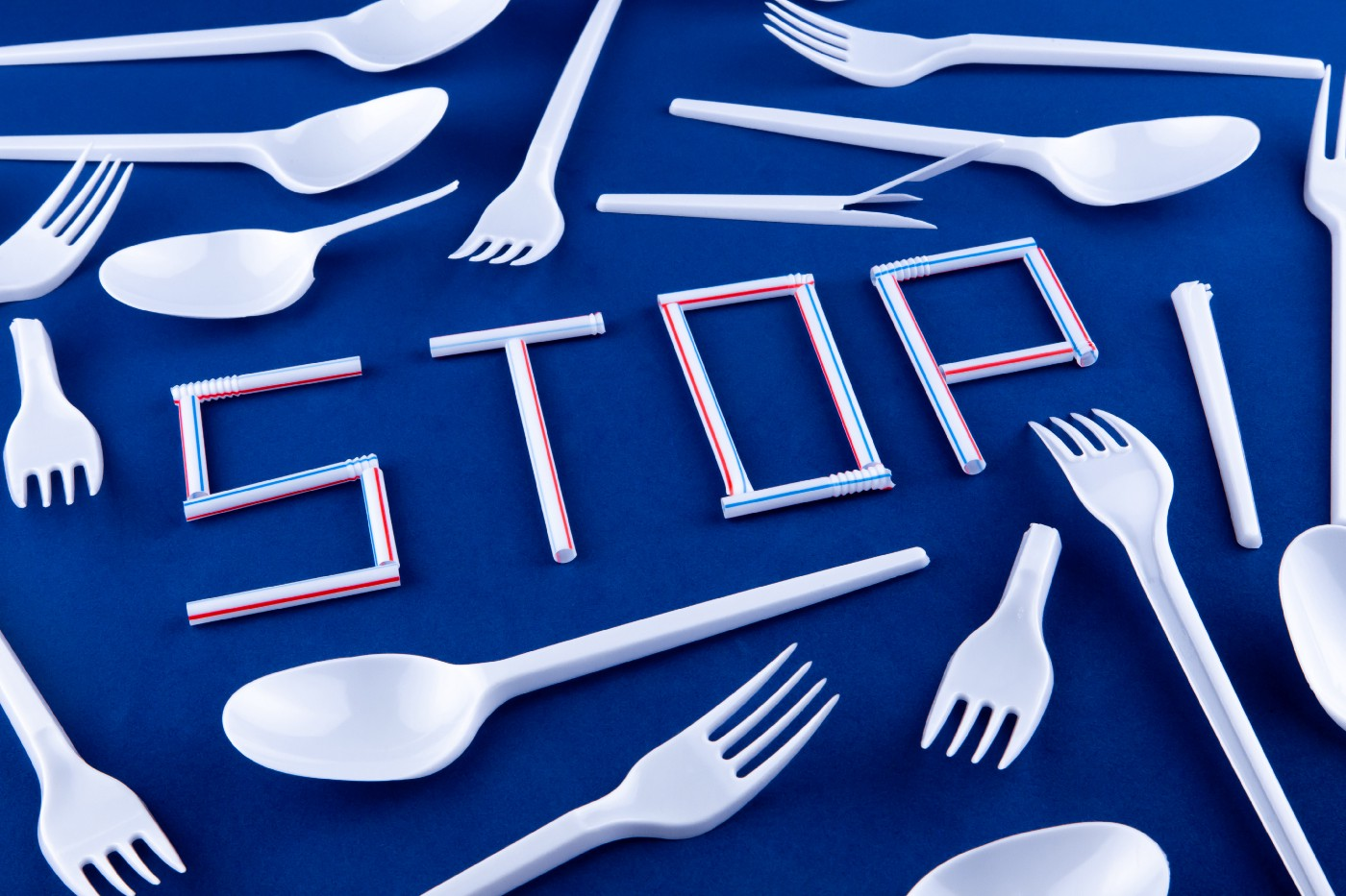 """Bunch of single-use plastics spread out on a blue table, with the word """"STOP"""" made from plastic straws, surrounded by many plastic spoons & forks."""