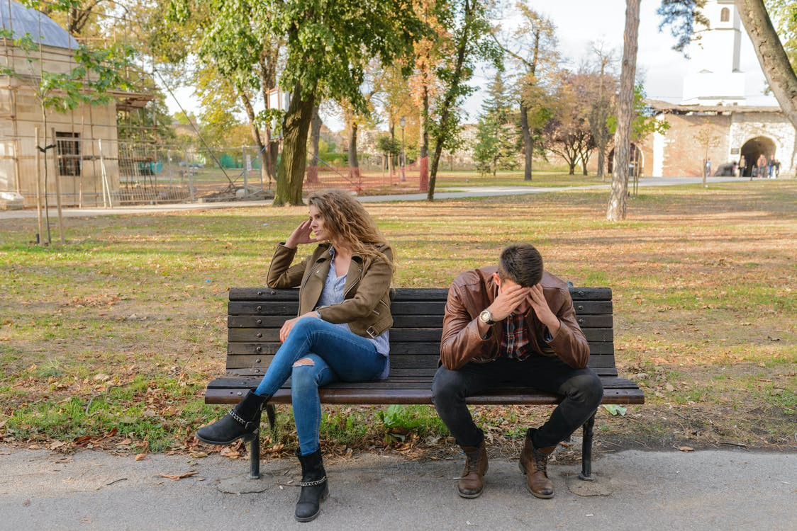 A couple sits on a bench together. One looks away, frustrated, and the other holds his head in his hands, exasperated. #argument #fight #relationships #dating #couple #disagreement