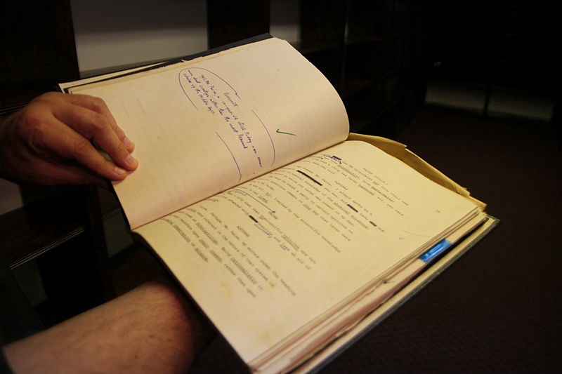 An open script book with written-in markings and corrections.