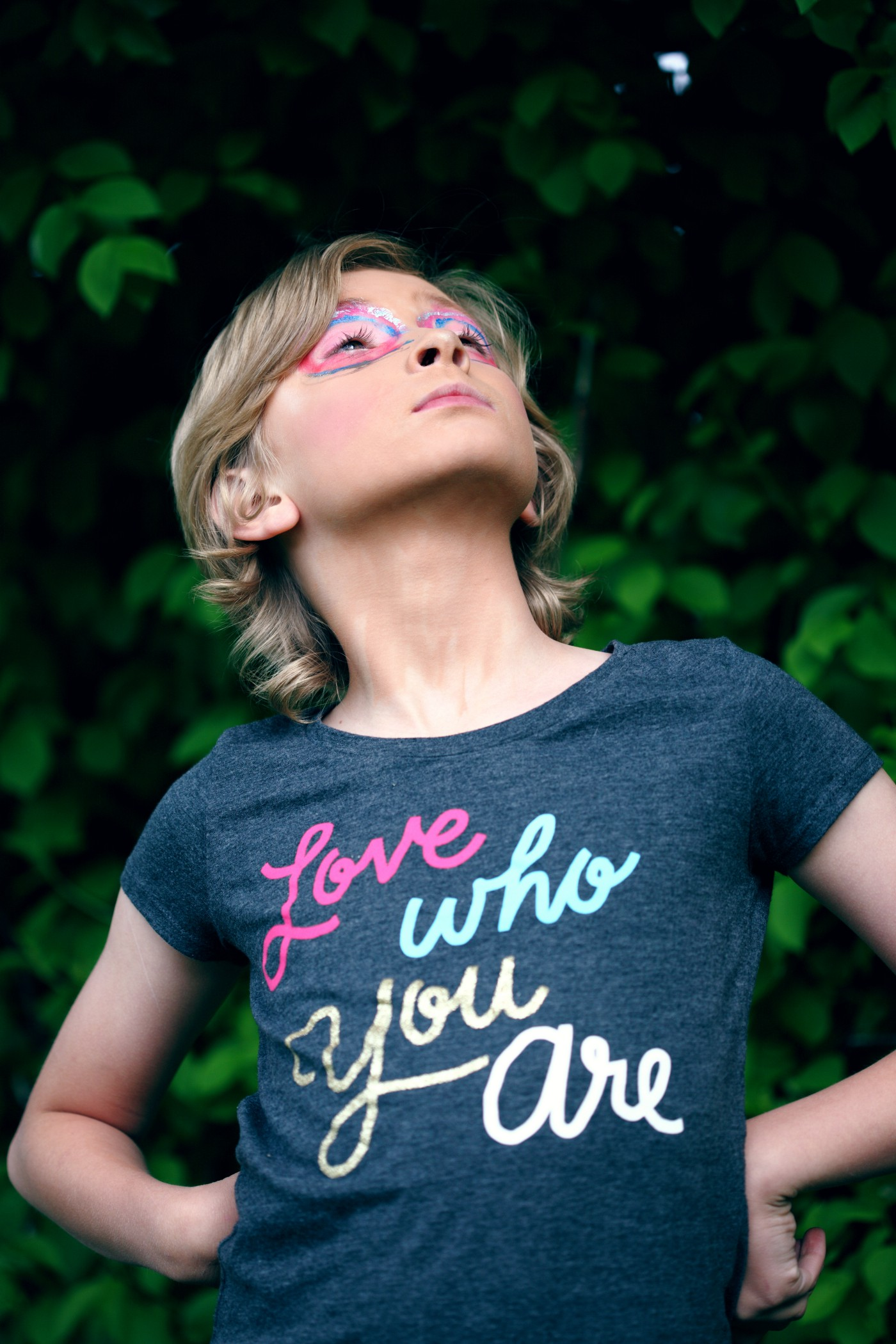 """A confident child looking up wears a shirt with the words, """"love who you are"""""""